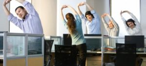 Office workers stretch before they get back to work --- Image by © Blue Jean Images/Corbis